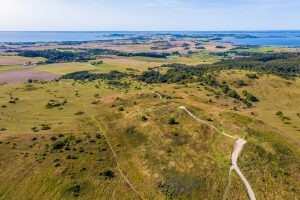 Mols Hills, Denmark - September  17, 2020 - Trehøje seen from above. The three Bronze Age mounds of Trehøje, 127 metres above sea level, offer a panorama view from Aarhus to Ebeltoft, including four inlets: Kalø, Begtrup, Knebel and Ebeltoft. From up here you can see the National Park's border to the south west, where fertile clay once deposited by the ice means the land is intensely farmed, as opposed to the nutrient-poor sand left by the ice on the hills and on the coastline along Ebeltoft Vig.