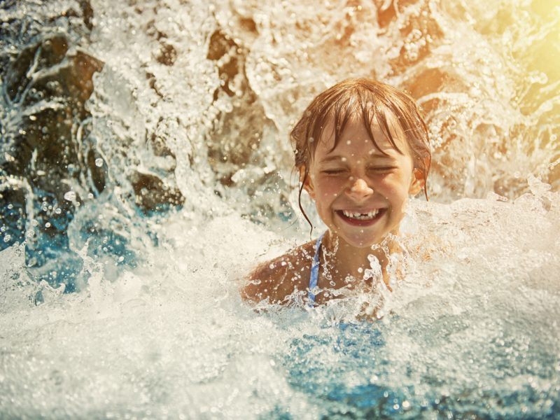 Little girl in waterpark pool being splashed by waterfall. Sunny summer day.