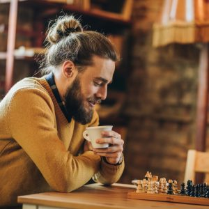 Young hipster man relaxing in a cafe and playing chess by himself.