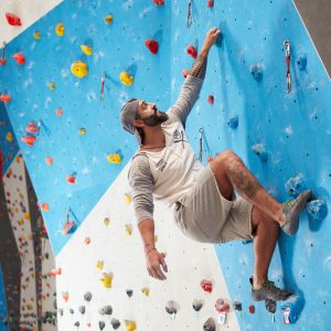 Low angle view of mature sporty man climbing wall in gym. Full length of fit male is exercising. He is in sports clothing.
